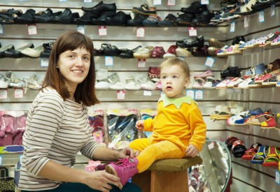 woman with child chooses baby shoes