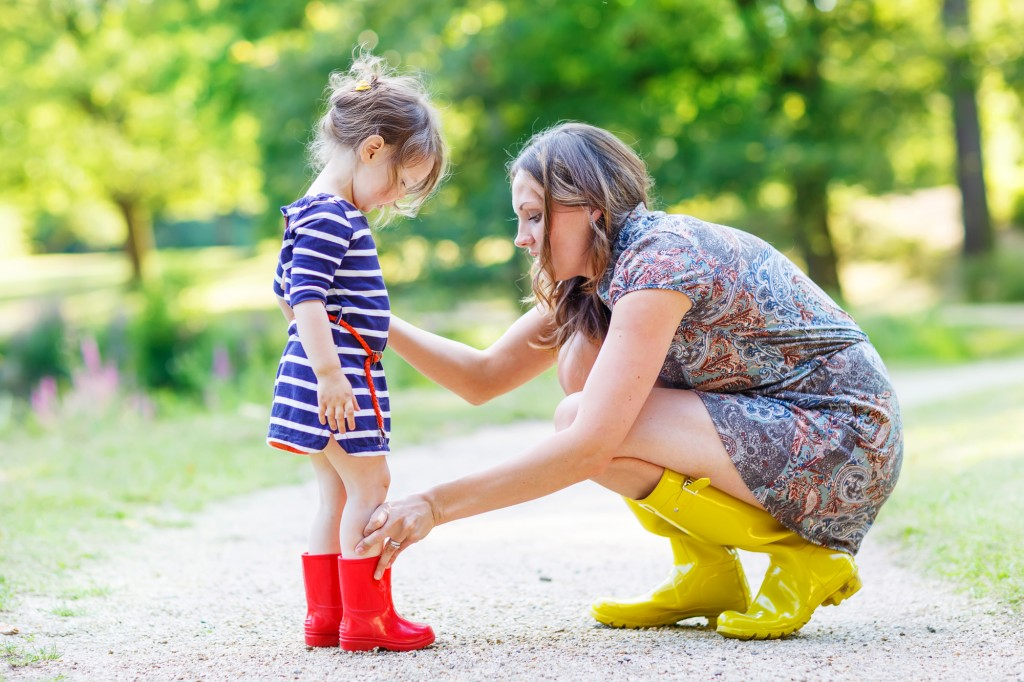 mother and little adorable child girl in rubber boots having fun