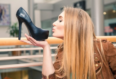 Woman kissing shoe. Women loves shoes concept.